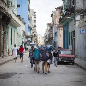Havana, Cuba - December 17, 2014: Four young women backpacking in Cuba walk down a street in Centro Habana in Havana.